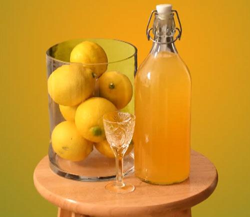 Лимончелло в бутылке и лимоны в стакане