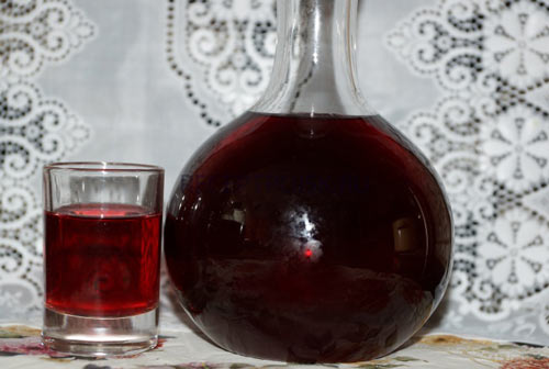 Графин и стакан на столе с наливкой из варенья