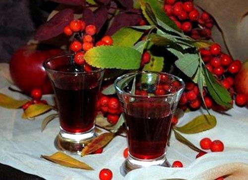 Вино в стакане и красная рябина на столе