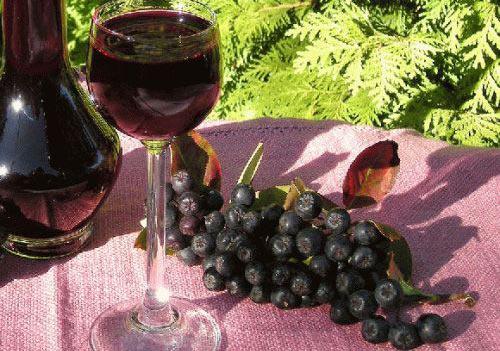 На столе наливка из черноплодной рябины и ягода