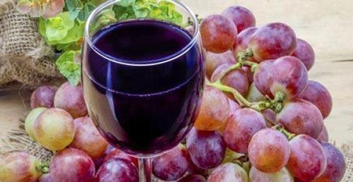Бокал с вином и виноград на столе.