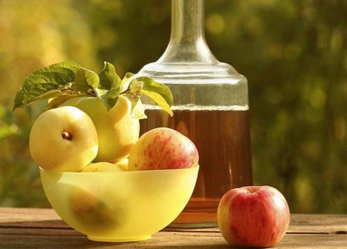Яблоки в вазе на столе и графин с вином.