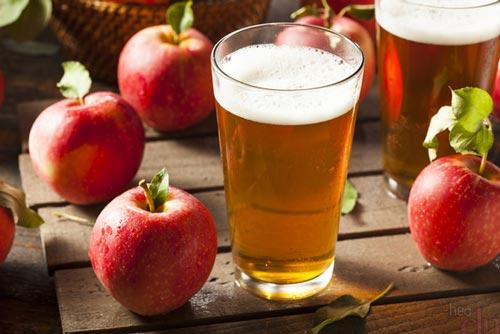 Вино в стакане и яблоки на столе.