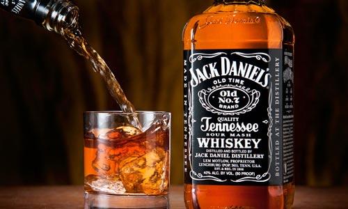 Виски Джек Дэниелс в бутылке и стакан рядом.