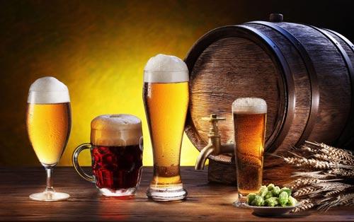 Пиво в разных бокалах и бочка рядом.
