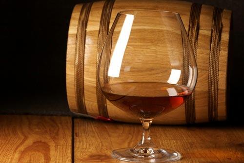 Рюмка с виски и бочка дубовая.