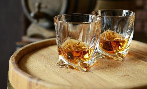 Виски в стакане на бочке.